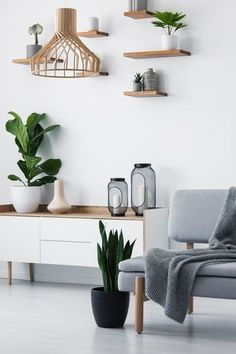 Wooden pendant light, simple shelves on a white wall and a plant By bialasiewicz. Wooden pendant l Living Room Paint, Home Living Room, Apartment Living, Tan Sofa, Scandinavian Interior Bedroom, White Walls, Home Interior Design, Interior Inspiration, Home Furniture