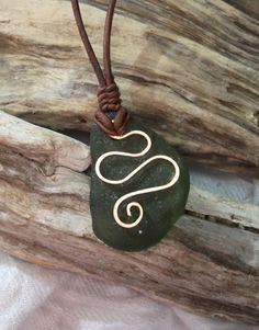 Beautiful Green Sea Glass necklace with a handforged copper swirl This piece has been braided onto a distressed red/brown leather necklace which is self adjusting to any size.