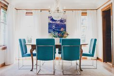 Milo Baughman re-edition chairs for Thayer Coggin were upholstered in custom fabric from Osborne and Little, brightening the space with a pop of turquoise. The chandelier and rug were the clients' own, and the curtains are custom wool sheer drapery fabricated by Lesley Petty Workroom with fabric from Kelly Forslund Showroom. Jennie Gruss Interiors