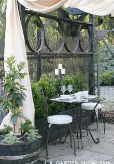 love the mix of elements in this patio dining area, featuring repurposed rusted metal circle elements (wine or whiskey barrel rings) -- 2009 L.A. Garden Show