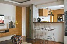 """Para as arquitetas Isabela Jock Piva e Adriana Cocchiarali, um apartamento pequeno não admite espaços compartimentados. """"Integrados, os ambientes têm pleno uso"""", avisa Isabela. Seguindo esse conceito, elas desenharam uma bancada de ipê de 2 m de comprimento que, elegantemente, traz amplitude e integra a cozinha à sala. Ao lado do fogão, duas folhas de madeira se abrem juntas, criando uma porta em L e aproveitando o espaço em quina da cozinha de 7 m2."""