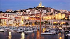 The Basilique Notre-Dame de la Garde looks down from the top of Marseille over boats in the city's historic harbor