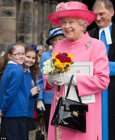 Smiling despite the rain: The Queen leaves Glasgow Cathedral with Revd Dr Laurence Whitley after attending a service of thanksgiving to mark her Diamond Jubilee