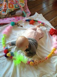 Voel en ontdekhoepel. Hiermee prikkel je de baby op verschillende punten. Namelijk veel felle kleuren dus zien ook verschillende stofjes dus voelen. Het is gemaakt van verschillende oude stofjes en andere dingen daarom recyclage. je kan dit gewoon op de speelmat van de baby rond hem leggen. De baby zal zeker gefacineerd zijn.