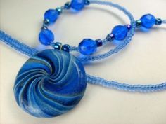 This cute candy land style lollipop pendant necklace has a beautiful swirl of pearl and matte blue polymer clays. This is a fun and boldly colored piece that shows how well polymer clay can be made to imitate glass. Shades of cobalt and sky blue are swirled with silver tones for an eye catching, candy-like effect.  The 1 inch disc is strung on nylon coated jewelry wire with glass and crystal beads in complimenting shades of blue. The pendant has been given a thin coat of water based…