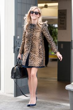 This is how to do leopard for the office. We love how Witherspoon teamed her RED Valentino coat with simple black accessories to let the statement topper take center stage. Red Valentino Leopard-Jacquard A-Line Coat, $640, available at Matches Fashion.