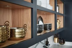 Typical shaker style open shelving is given a contemporary twist with discreet lighting to showcase gleaming copperware.