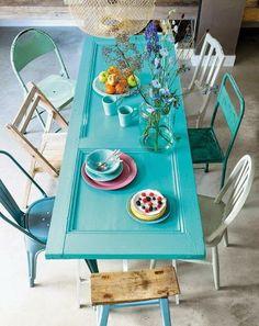 Una de las opciones más interesantes es la de convertir esta puerta en mesa. Podemos usarlas en cocinas y comedores, dependiendo de su tamaño. Son ideales, pues pueden pintarse de cualquier color. Tan sólo necesitaremos unas patas, que perfectamente pueden ser caballetes, y unas cuantas sillas. Y si deseamos innovar, podríamos añadirle sillas diferentes, para darle más dinamismo.