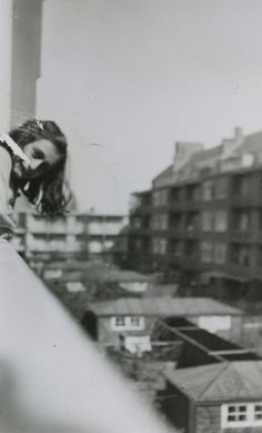 Anne Frank pokes her head out of the window of the family's flat at Merwedeplein, Amsterdam, 1942.