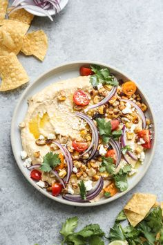 This spicy hummus recipe is topped with charred fresh corn, cherry tomatoes, red onions and zesty lime juice. Perfect for summer entertaining + picnics!