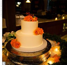 Small two-tiered cake. The two layers were frosted with buttercream and decorated with orange flowers.