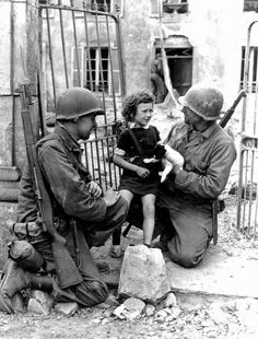 Two American soldiers try to comfort an upset girl with a puppy. [World War II, 1944]