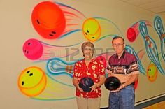 Two bowlers with bowling balls against a colorful wall at the alley  Stock Photo