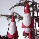 """Make an easy Santa Ornament:   Red construction paper, White bond paper, Red felt-tip marker, White craft glue, Clothespin, Needle, Red thread for hanging loop, Compass.  ~On construction paper, draw a circle 11-1/2'' in diameter with compass. Cut out. Cut into 4 equal pie-shaped wedges. ~For each wedge, draw a Santa face on white bond paper with marker. Cut out. Glue to wedge. ~Lap one straight edge of wedge 1/2"""" over the other to form; glue in place. Hold with clothespin until glue dries."""