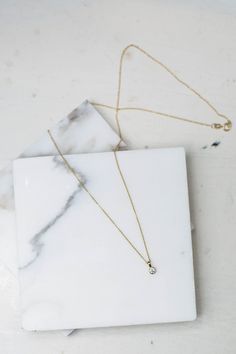 simple diamond necklace from Diamond Foundry on marble slate coaster