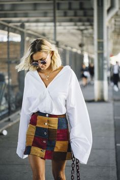A billowy white blouse gives a modern upgrade to a vintage skirt. #streetstyle