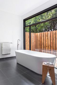 Modern bathroom with large window and gray floor tiles | Usual House