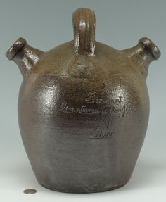 Low Estimate $2,500   Important East Tennessee decorated Presidential presentation harvest jug. Harvest jug with extruded handle and two opposing spouts with two sine waves around the upper shoulder and an additional closed sine wave at the tip of the jar, resembling a sun motif. Possibly potted by Lewis Manning Haun (Greene County, TN, born 1835). Similar harvest jug forms attributed to L. M. Haun have are known. However, none of these jugs have retained the handle like this example.