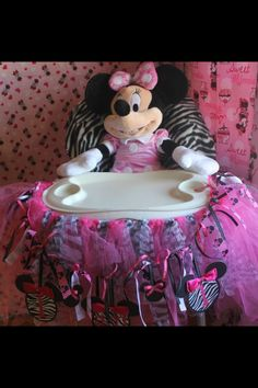 Minnie mouse high chair decorations made from tule and ribbion also used a minie mouse cricket cartridge to cut out minnie mouse head shapes