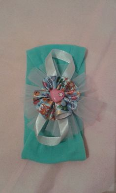 Faixa de meia de seda para bebê com flor de fita de cetim e detalhes em tule e aplique de coração. R$ 8,00