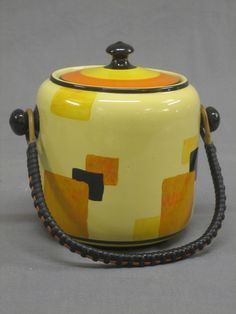 A circular Art Deco Edna Best pottery biscuit barrel and cover
