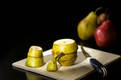 sliced pieces of pear near kitchen knife stand on wooden board with