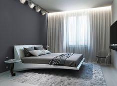 Grote verlichting blikken geven een dramatische look aan deze moderne slaapkamer regeling, die een praktische hoeveelheid licht boven het hoofdeinde voor het lezen.  De gordijnen krijgen een zachte gloed van een profielkrans licht.