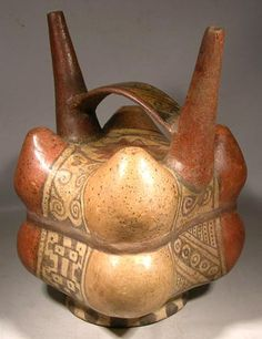 Lambayeque Stirrup Vessel — Peru  700 AD - 1300 AD  An unusual Lambayeque stirrup vessel from the Sican area of northern-coastal Peru. Eight conjoined globular objects with two tall tapering spouts and an arched handle. Beautifully polychrome painted with exquisite detail and a nicely burnished surface