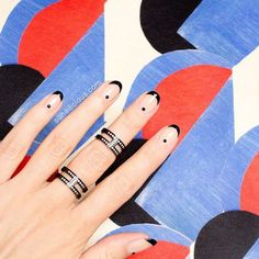 Amp up your nude nails with black dots and tips.