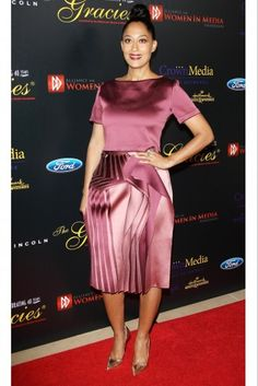 Tracee Ellis Ross wears a cranberry colored crop top and satin skirt with gold heels. | essence.com