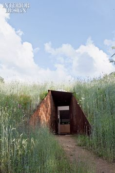 Dutch Architecture Firm Denieuwegeneratie's experimental, super-sustainable house just outside Amsterdam. Under the Hill : The entrance is formed from plates of recycled steel. Photography by Robertholden/photofoyer.