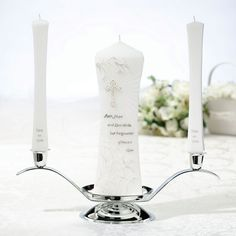 """Lillian Rose Christian Unity Candle and Two Tapers This wedding candle set includes two taper candles (9"""" tall) and one pillar candle (9"""" tall and 3"""" wide). The pillar candle is decorated with gold, brown and silver design that includes vines, a cross, light rays and the verse """"Faith, Hope and Love abide, but the greatest of these is Love."""" Each taper candle is decorated with the words """"Two as One."""" Candle holder in picture is not included. Price $47.90"""