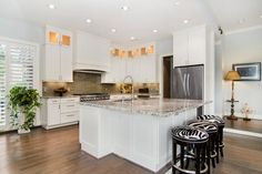 HGTV invites you to take a look at this modern kitchen with white cabinets, a gray glass tile backsplash and funky zebra print stools.