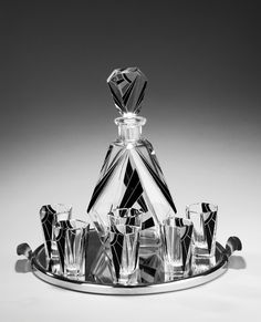 An Art Deco Period Decanter Set By Karl Palda: This set consists of the decanter, six ensuite glasses and a tray. Typical for this range and type of glass by Karl Palda, the famed Bohemian manufacturers is the technique of using enameled glass into which art deco patterns of foliages, clouds, bolts and sun rays were wheel carved. It is in excellent condition throughout. Circa 1930 | Exhibitor: William Cook