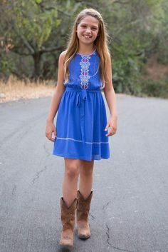 Vibrant sky blue flowing chiffon is decorated with intricate tribal patterns on the bodice and neckline of this captivating girls' dress, creating a perfect look for spring holidays and photos, especially when paired with our rugged western-inspired Sidewinder Boots (pictured here and sold separately). Fully lined underneathSash tie beltEmbroidered necklineButton closure in backDesigned by Blush