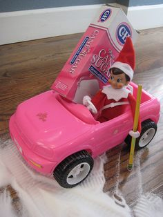 Elf on a Shelf doing spins in Barbie's car.