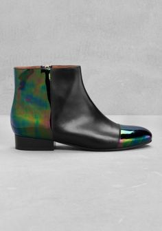Crafted from a material-blocking leather and an oily-like finish, these elegant ankle boots feature an edgy design.