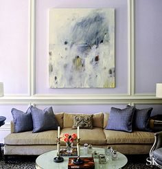 Suzanne Kasler - purple walls with white trim, purple cushions on this mustard brown modern low sofa, round coffee table