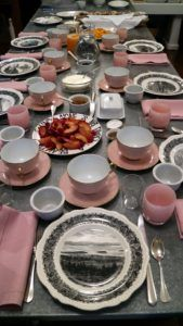 "Breakfast for my friends was served in the kitchen on the large galvanized topped table. I have many sets of dishes and on this morning I used the plates of Mount Desert, a Staffordshire pattern of transferware depicting the scenes of Acadia Park. The pink cafe au lait cups are Limoges, and the pink glasses come from Glassy Baby. The modern plates piled high with fruit were made for me by Rob Wynne, a New York artist.  ""A beautiful sound alone is not enough"", says this plate."