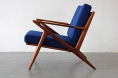 5 mid-century modern chairs with blue upholstered cushions and wooden frame that we love.