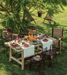 A mesa, em meio ao verde, é cheia de detalhes rústicos. Caso o calor aperte, o chapéu protege do sol
