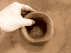 Ceramics: Pottery handbuilding techniques tutorial. How to make pinch pot head planters. Step 2: pinching and pressing the clay upward with thumb and index finger