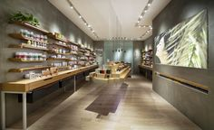 Pure Swiss store by UniteUnit, Hong Kong  The appealing central floating display module by wood flitches remains the main feature over the store. The rolls of felt drawers help to softened the angular feature and maximize the storage space. A dynamic wall display acts as a balance within the angular space, by contradicting to all angular fixtures, the wall display is constructed by bend plywood, it is flexible for tall or short items and definitely enhancing the aesthetic and flow of the…