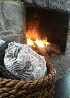 basket with blankets next to fireplace - love the large basket