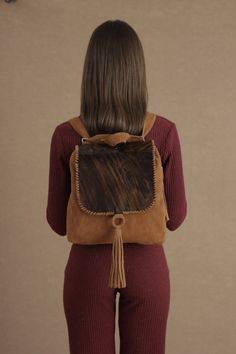 """Calf Hair Leather Flap. Top zip closure. Big Front Tassel Adjustable straps allows to use as a backpack or shoulder bag Inside is fully lined with one zipper pocket and one open pocket  Length: 31cm/ 12,2 """" Height: 31cm/ 12,2"""" Depth: 8cm/ 3,1 """"   This bag is ready to ship. Please allow 3/4 days to arrive any destination"""