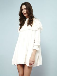 Silky-feel white swing mini dress with lace upper, subtle frill detail, and gathered cuffs.  Fabric Composition: Lace 100% Polyester, Main: 65% Viscose, 35% ...