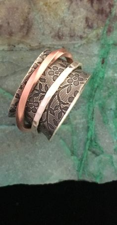 Our floral spinner ring design with a slightly twisted copper spinner and one hammered silver spinner.  Perfect for the fidgeters, the anxious, and those who want their ring to wear a ring!
