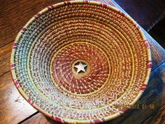 Coiled medium size bowl from Florida pine needles. Top maroon coil added for color.  Simple, wrapped, fern and diamond stitches used for interest.  Silver plated five point star in bottom