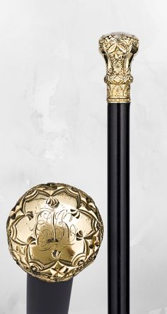 "This handsome walking stick is topped by a gold knob handle featuring an  elaborate engraved and chased motif of bold scrolls and delicate  flowers. The crown of the handle bears the initials ""ENK."" ~ decorative canes and walking sticks ~ M.S. Rau Antiques"