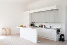 The bright kitchen furniture from Finnish Saari was supplemented with a site-built bench that allows the kitchen work with views through the tall windows. Bar stools by Alvar Aalto - Sköna Hem, Sweden.